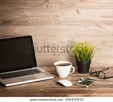 Wooden office interior, table with laptop, cup of hot coffee, mouse, glasses, smartphone, earphones and pot plant, in dramatic light vintage toned. - stock photo