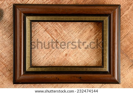Wooden old photo frame on old wooden background.
