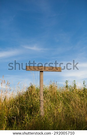 Wooden old road sign pole and blue sky with clouds on background with green grass - stock photo