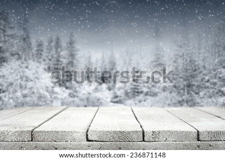 wooden old table with frost and forest on background  - stock photo