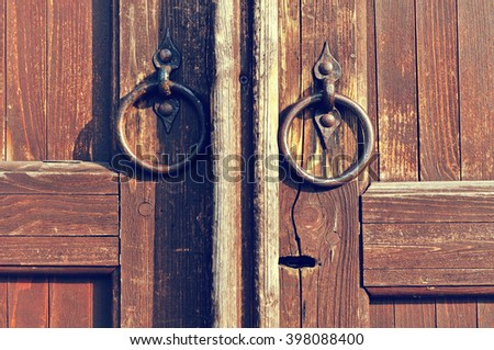 Wooden old weathered door with keyhole and  worn metal door handles in the form of ring. Architectural detailed background in retro tones  - stock photo