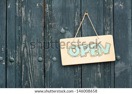 Wooden open signboard hanging on planks background - stock photo