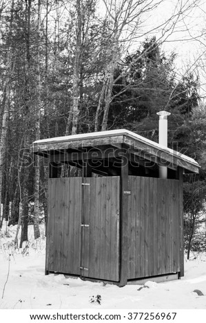 Wooden outhouse in winter black and white image