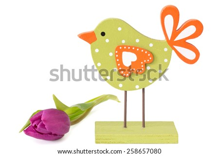 Wooden painted bird with violet tulip on white background - stock photo