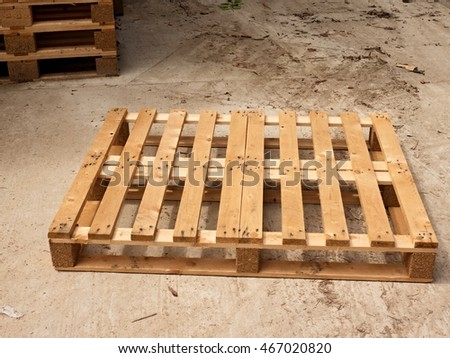 Wooden pallet on worn out concrete ground. Empty pallet ready for packing and shipping