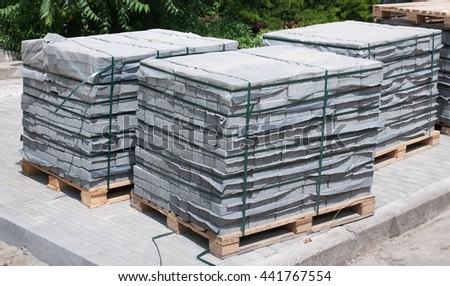 Wooden pallets with square gray concrete pavement tiles simulating surface cobblestone. Stack pallets of paving stones. - stock photo