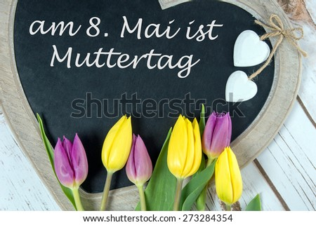 Wooden panel in heart shape with tulips and the german words Mother Day / Mother Day - stock photo