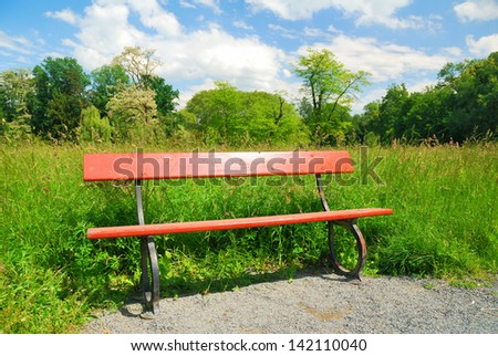 Wooden park bench in springtime greenery - stock photo