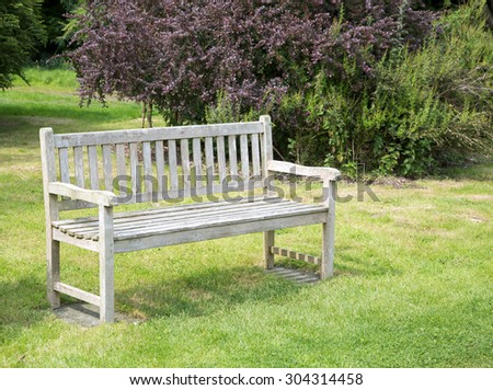 Wooden park bench in tranquil garden - stock photo
