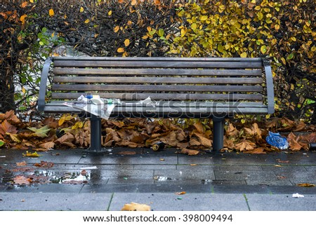 wooden park bench with wet newspaper on rainy autumn day