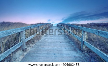 Wooden path at Baltic sea over sand dunes with ocean view        - stock photo