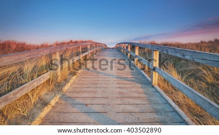 Wooden path at Baltic sea over sand dunes with ocean view, sunset summer evening                           - stock photo