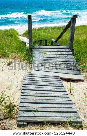 Wooden path down to the beach and ocean.  Walkway and stairs through sand dunes and grass. - stock photo