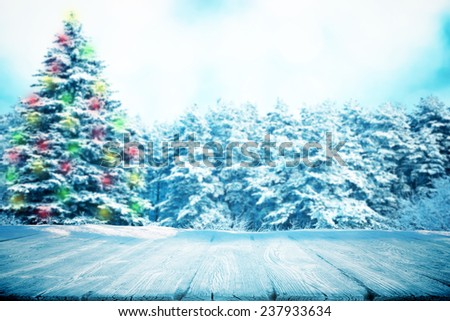 Wooden path in snow in forest with color fir tree in garland - stock photo