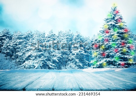 Wooden path in winter forest with big fir tree in color lights of garland - stock photo