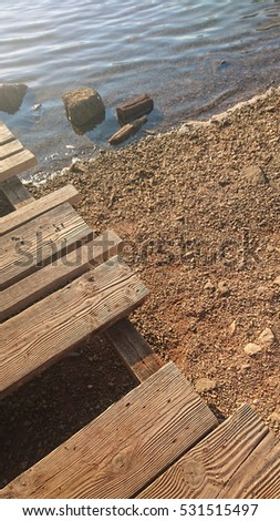 Wooden Path over rough Beach and natural water upright