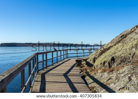 Wooden Pathway or Footpath near lake. Path along the water on sunny day. Beautiful landscape with way between stones and lake. Wooden Bridge with handrails turning. Swedish nature. Place for your text - stock photo