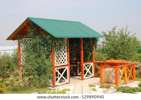 Wooden pavilion twined by Clematis in the summer garden