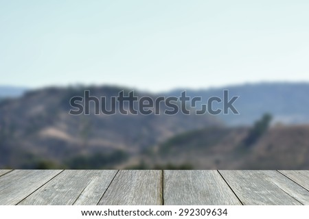 Wooden paving  blurred  background of mountains and sky. - stock photo