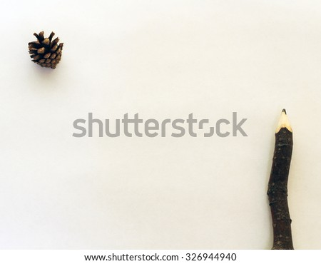 Wooden pencil and pine cone as minimal background for templates layout