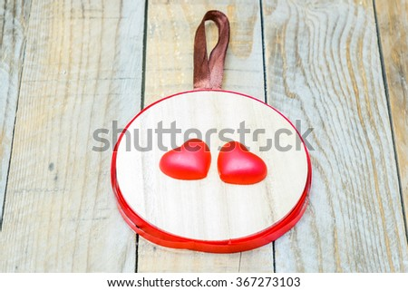 Wooden pendant with two red hearts in the center