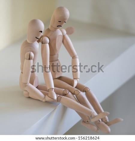 Wooden people sitting at home and supporting each other. People relationship concept. Drawn faces - stock photo