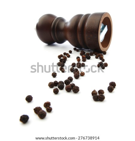 Wooden peppermill with peppercorns isolated on white background - stock photo