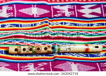 wooden peruvian flute with traditional cloth - stock photo