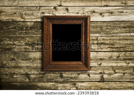 wooden photo frame on old wooden wall - stock photo