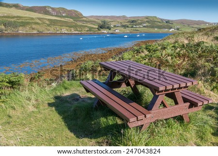 Wooden picnic table and benches at the shore of Loch Harport, Isle of Skye, Scotland - stock photo