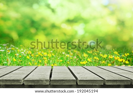 Wooden picnic table near summer flower field - stock photo