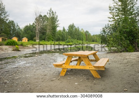 Wooden picnic table sits on the mud beside a stream in the forest wilderness of Alaska. - stock photo