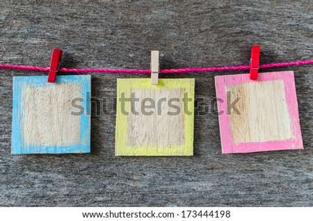 wooden picture frame hanging on clothesline on wood background. - stock photo