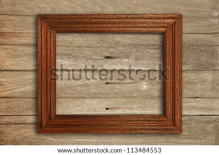 Wooden picture frame on old wooden wall