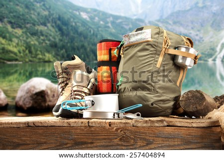 wooden pier and backpack and shoes of brown color and lake of green color at summer time  - stock photo