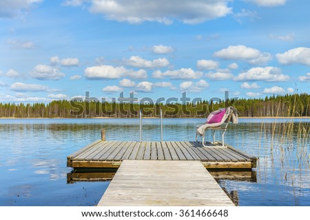 Wooden pier and cozy bench with soft blanket and pillows on a background of the beautiful lake and forest at sunny day.Picturesque natural landscape.Panoramic view.The land of lakes.Finland.Europe. - stock photo