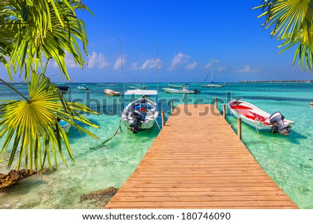 wooden pier and fishing boats on a Caribbean beach with transparent waters - stock photo