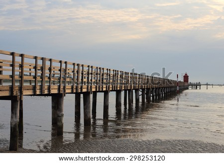 Wooden pier and lighthouse in Lignano Sabbiadoro, Italy
