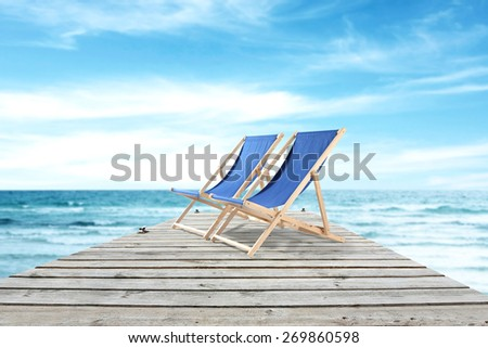 wooden pier and summer chairs  - stock photo