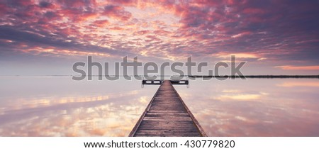 wooden pier at Lake Neusiedl at sunrise near Podersdorf, Burgenland, Austria