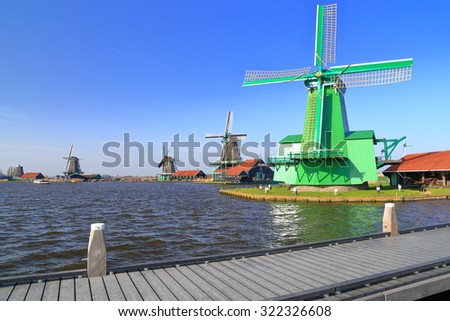 Wooden pier by and green wind mill near the lake shore in Zaanse Schans, Holland - stock photo