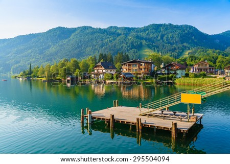 Wooden pier for boats on shore of Weissensee alpine lake in summer landscape, Austria - stock photo