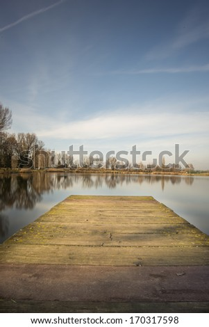 Wooden pier in beautiful lake - stock photo