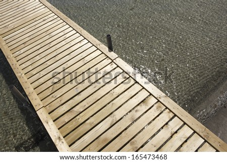 wooden pier in crystal clear water and tiny waves - stock photo