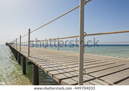 Wooden pier jetty going out from tropical beach into ocean