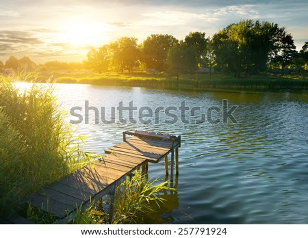 Wooden pier on a river in evening - stock photo