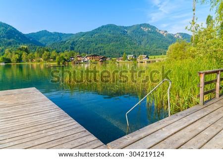 Wooden pier on shore of Weissensee alpine lake in summer landscape, Austria - stock photo