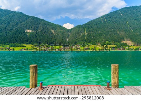Wooden pier on shore of Weissensee lake in summer landscape of Alps Mountains, Austria - stock photo