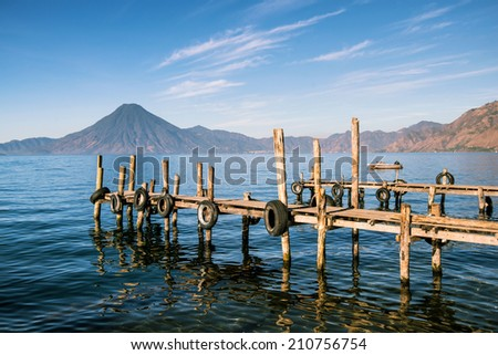 Wooden pier on the peaceful lake Atitlan in Guatemala and volcano - stock photo