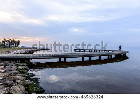 Wooden pier on the sea at sunrise, businessman walkin on pier